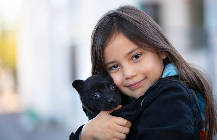 Young girl hugging a small black puppy