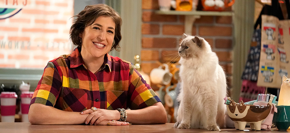 Mayim Bialik posing with a Siamese type cat