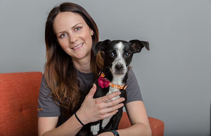 Woman holding a black and white dog wearing a Best Friends collar with a pink flower on it