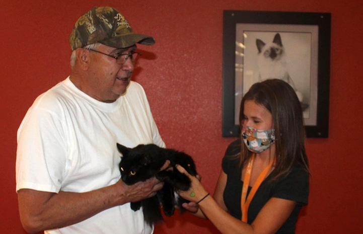 Woman handing Miss Corona the cat to David