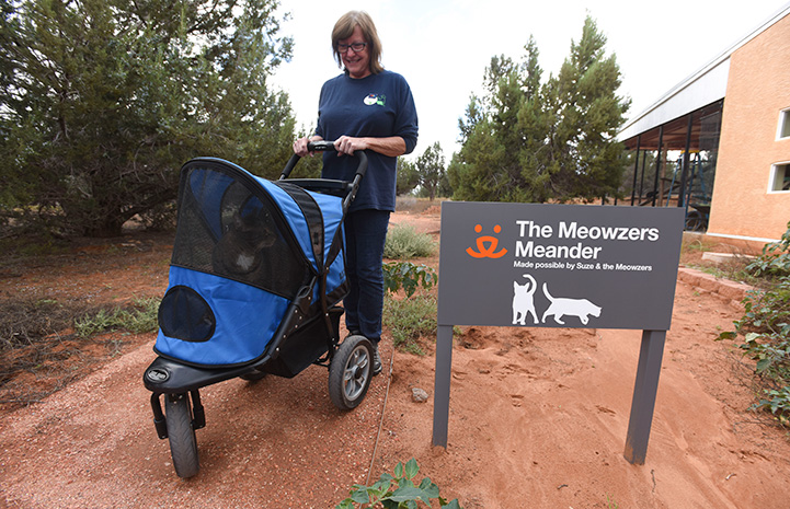 Woman taking a cat on a stroller ride next to a The Meowzers Meadow sign
