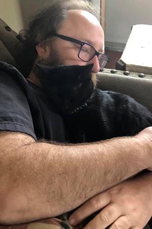 Daniel Miller lying down and hugging Jordan the cat