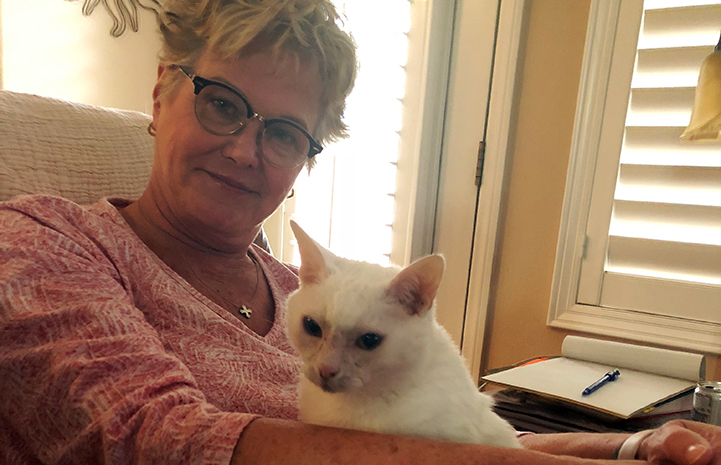 Adopter Dianne Beckman holding white cat Sonya on her lap
