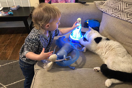 Russell the cat lying on the couch next to a toddler who is playing with a doll that lights up