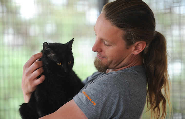 Cat World caregiver Levi Myers cradling a black cat in his arms
