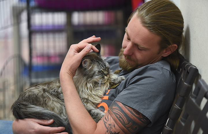 Caregiver Levi Myers sitting in a chair and cuddling Slader, a brown longhair tabby cat