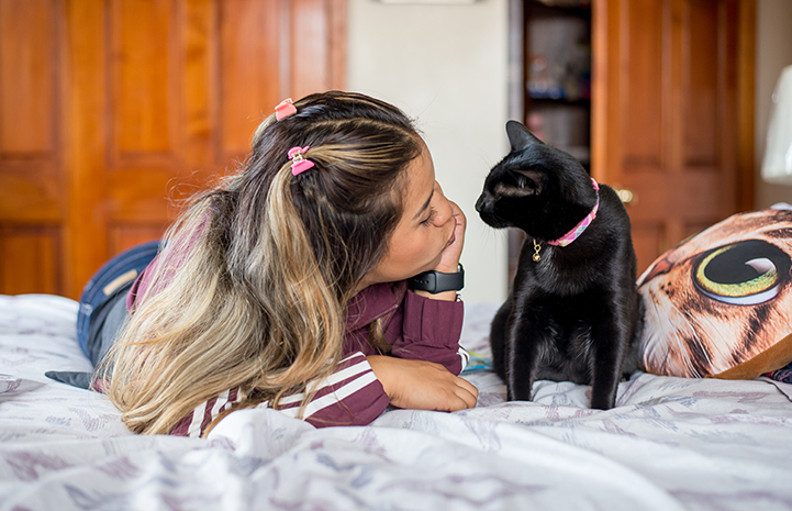 Vanessa Hernandez lying on the bed with Bella the black cat