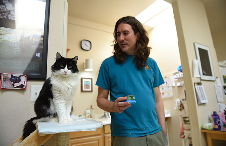 Zorro, the black and white tuxedo cat, sitting on a cat tree next to caregiver Eric, who is holding a can of food