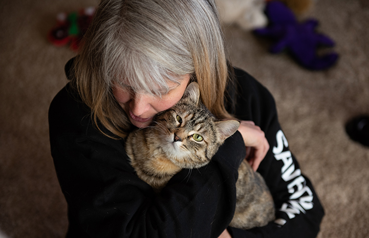 Birdie the tabby cat being held and hugged by the woman who adopted her