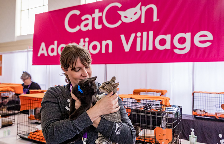 Woman holding two kittens in front of a CatCon Adoption Village sign