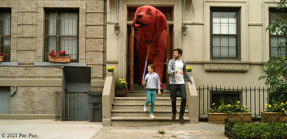 Clifford the Big Red dog walking on a leash out of a door with two people with copyright