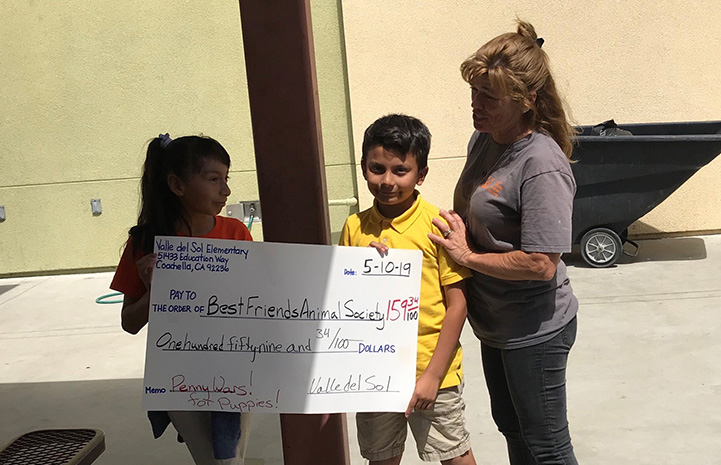 A large check to Best Friends Animal Society being held by a woman and two kids