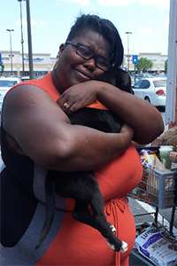 Carra hugging and holding Cocoa Puff, the puppy her husband just adopted for her