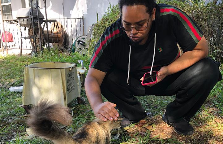 Dereck petting the head of a fluffy tortoiseshell community cat