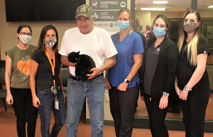 Stanislaus Animal Services Agency staff standing next to a man holding Miss Corona the cat
