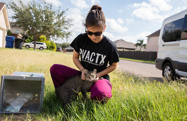 Woman wearing a PVACTX T-shirt sitting on the ground with an ear-tipped cat in her lap
