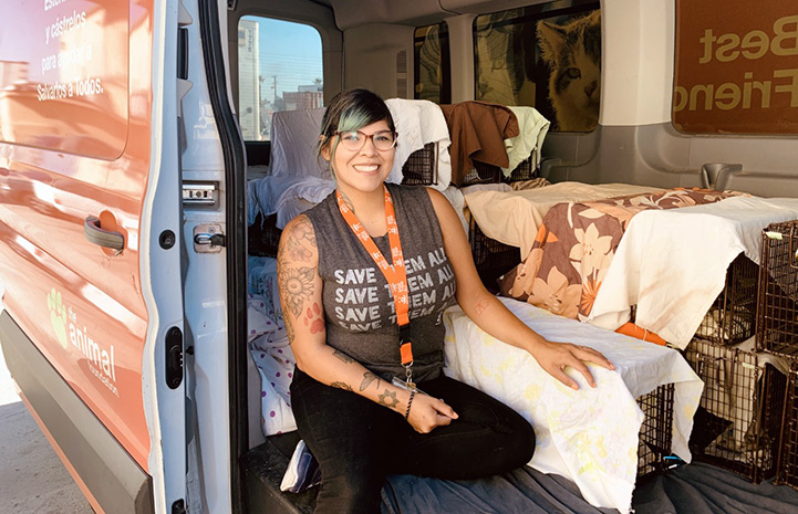 Woman wearing a Save Them All T-shirt in a van with a bunch of covered humane traps