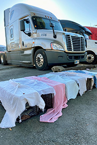 Row of humane traps covered in sheets lying in front of a truck
