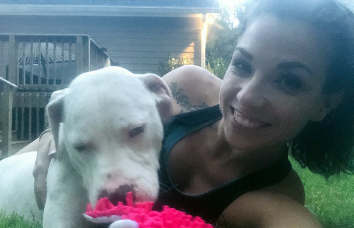 Selfie of woman lying on some grass next to Sailor the dog