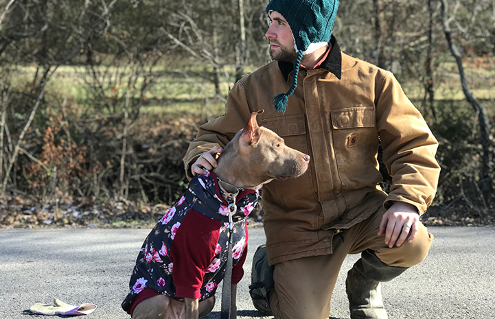 Man bundled up in winter weather protective clothing next to Kiwi the dog in a sweater
