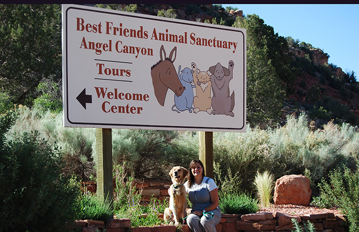 Ava the dog and a woman sitting under the Best Friends Animal Sanctuary sign