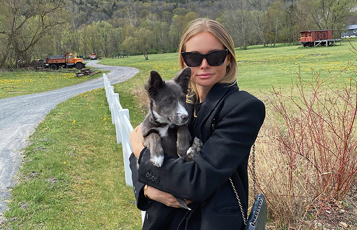 Claire Rose holding Billie, the puppy she adopted, in a grassy field