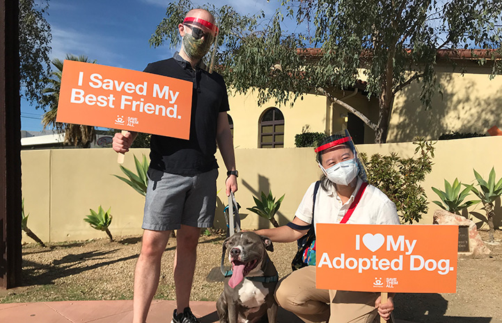 """Two people holding signs, saying """"I saved my best friend"""" and """"I heart my adopted dog"""" while next to Cannoli the dog"""