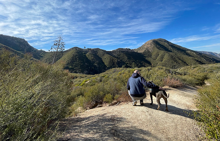Person and Cannoli the dog on a trail surrounded by hills