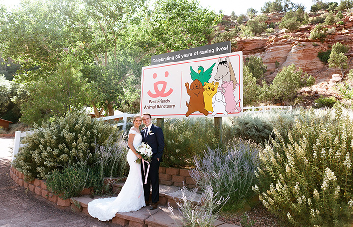Haley and Kevin in their wedding clothes in front of the Best Friends Animal Sanctuary sign