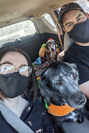 Two people in a car with Hubie and another dog