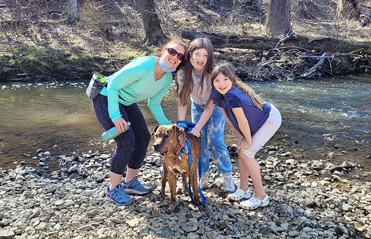 The family with Pancho the dog, next to a stream