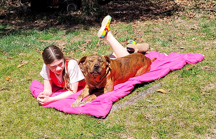 Pancho the dog lying on a pink towel with eyes closed in happiness next to a young girl