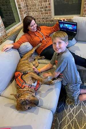Woman and young boy next to Pancho the dog who is lying on a couch