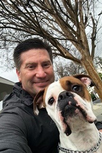 Roscoe and his adopter, outside under some trees without leaves