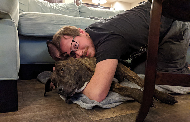 Person snuggling with Bonnie the dog in front of a couch