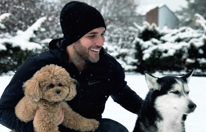 Tyler Rich with dogs Abby and Charlee playing in the snow