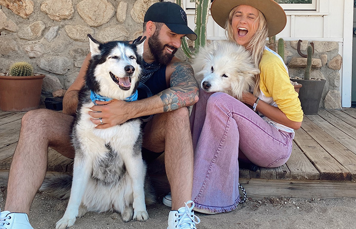 Tyler Rich and his wife smiling and posting with two dogs