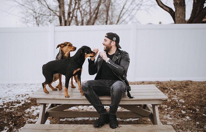 Tyler Rich sitting on the top of a picnic table with two dogs