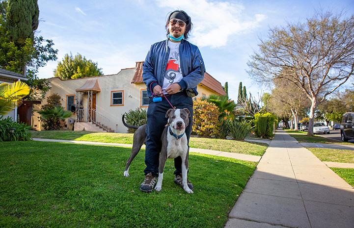 Man walking Neville the dog outside on a leash