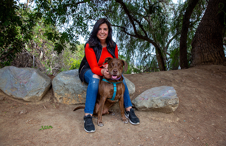 Trish Escobedo sitting on a rock with Jarvis the dog sitting in front of her