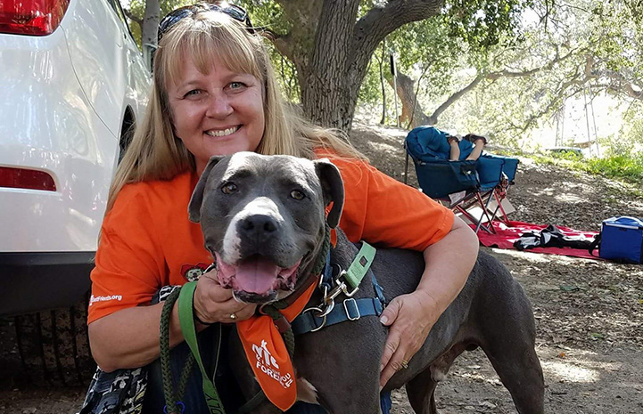 A woman wearing an orange T-shirt hugging a pit-bull-terrier-type dog while on a walk