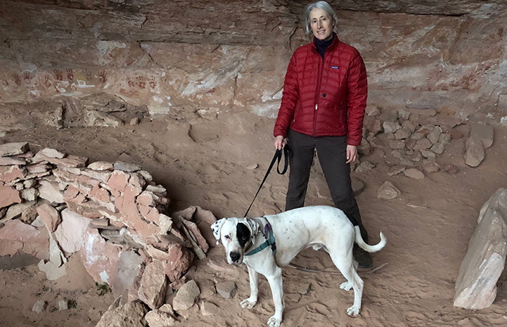 Volunteer Heather Harding with Peter the dog hiking in a cave area