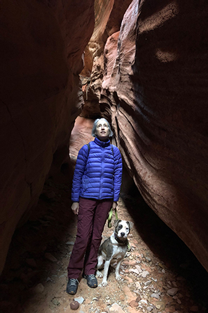 Volunteer Heather Harding hiking with Pilsner the dog in a slot canyon
