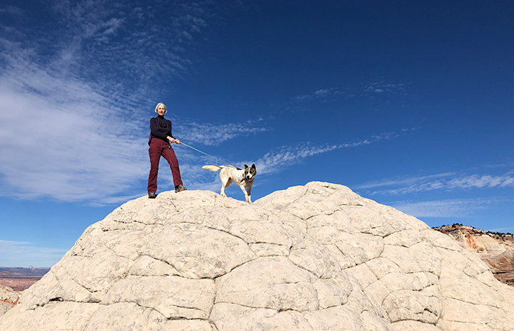 Volunteer Heather Harding hiking with Sun the dog on top of a beautiful rock formation with blue sky and clouds behind them