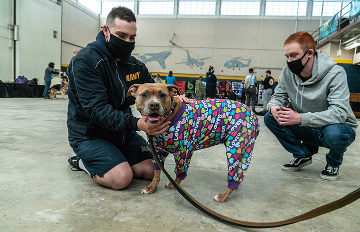 Two masked men from military base posing with a smiling brown and white dog wearing pajamas