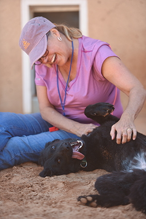 Woman smiling and sitting on the ground giving a belly rub to Rhonda the dog