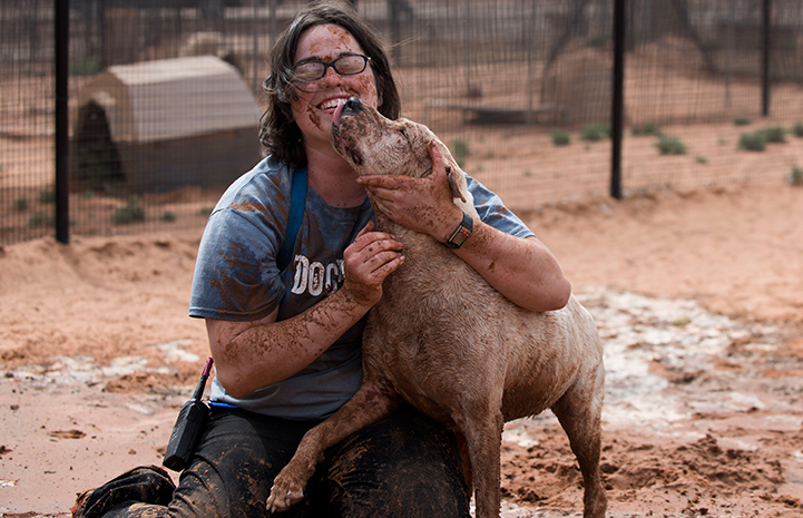 Caregive Haylee huggin Yuma the dog, both very muddy