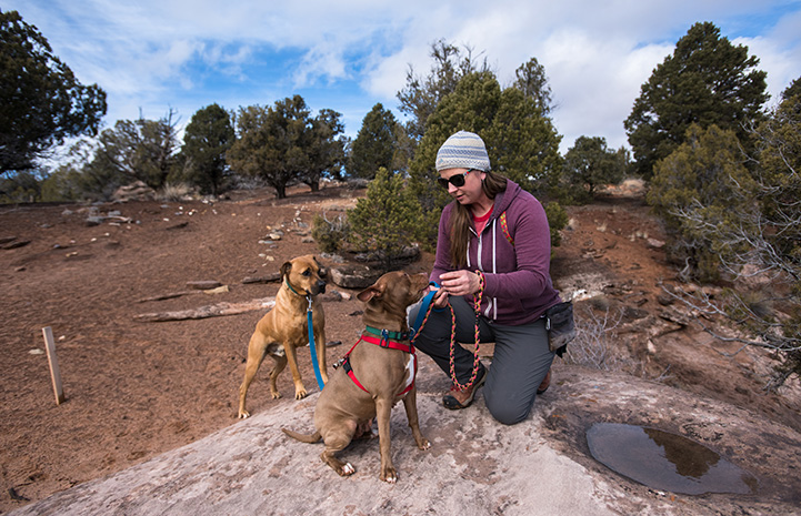 Dogtown caregiver Jess Cieplinski taking a hike with dogs Cosette and Cleveland