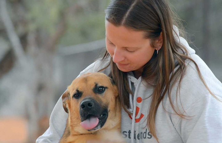 Dogtown caregiver Jess Cieplinski hugging Klaus the dog