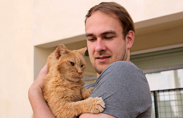 John holding Lionel the senior orange tabby cat